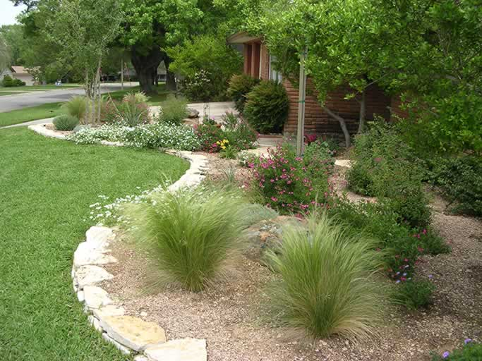 A well groomed lawn juts up against a contained area of hearty plants in loose gravel