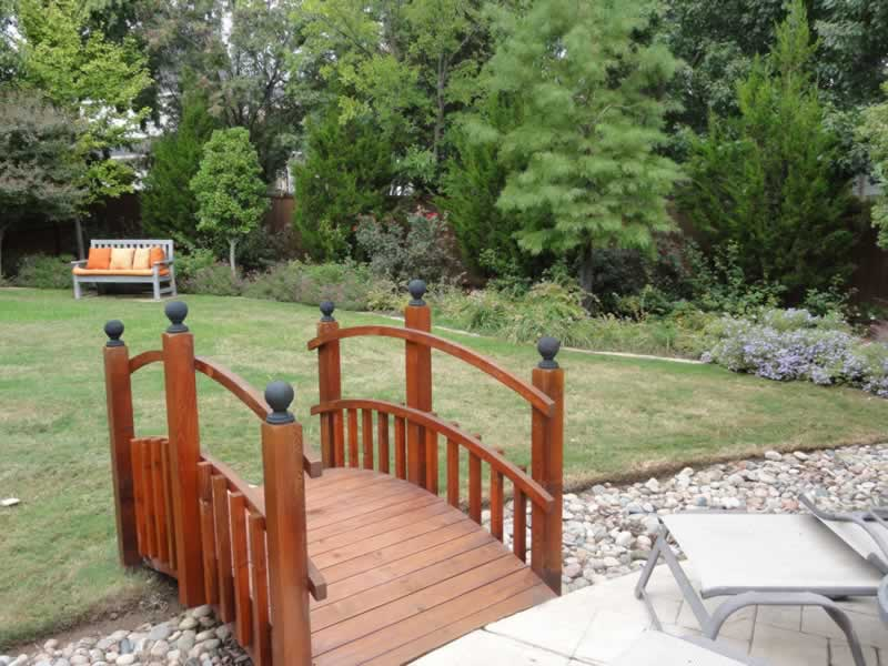 A decorative redwood bridge crosses a stone path in an Aledo back yard