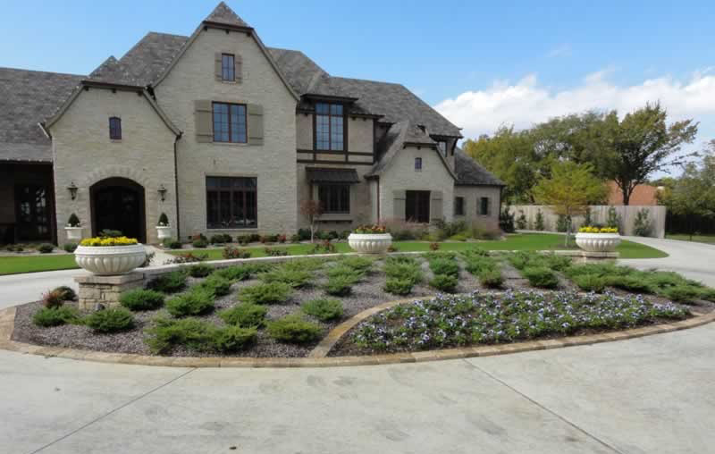 Driveway roundabout landscaping in front of a Colleyville home