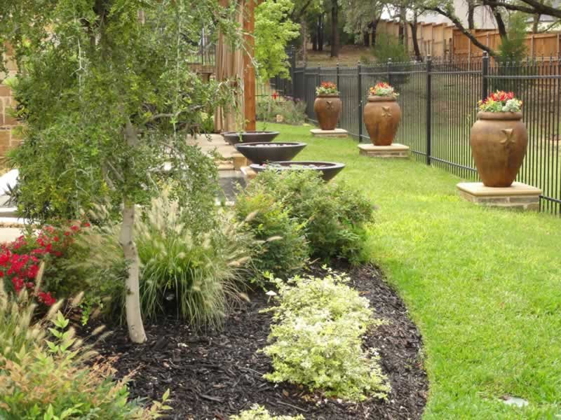 Landscaping features line a Southlake backyard - Landscape Design In Southlake, TX Landscape By Design