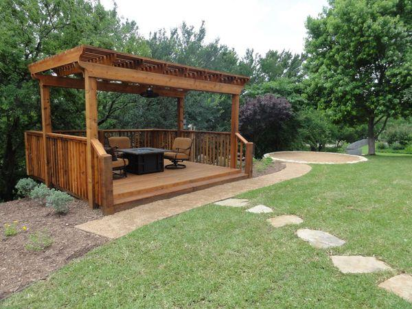 Freestanding pergola with patio furniture in a residential backyard