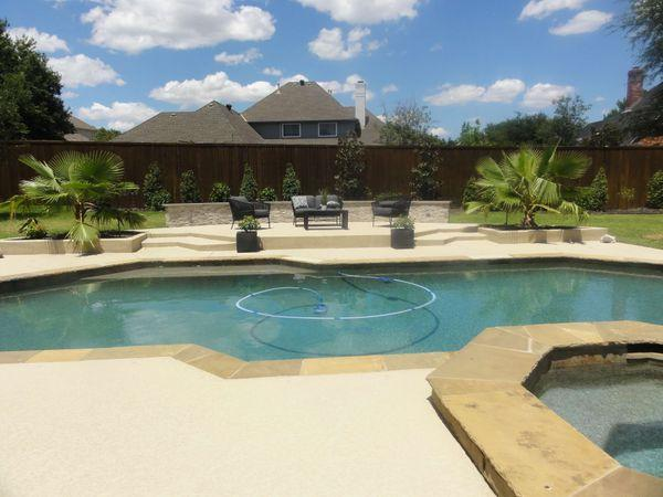Residential backyard with a pool and upgraded pool decking and patio