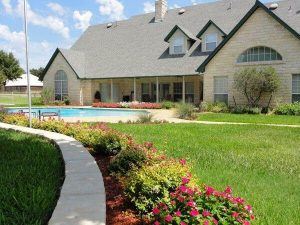 The backyard of a residential house with a pool and newly landscaped yard.