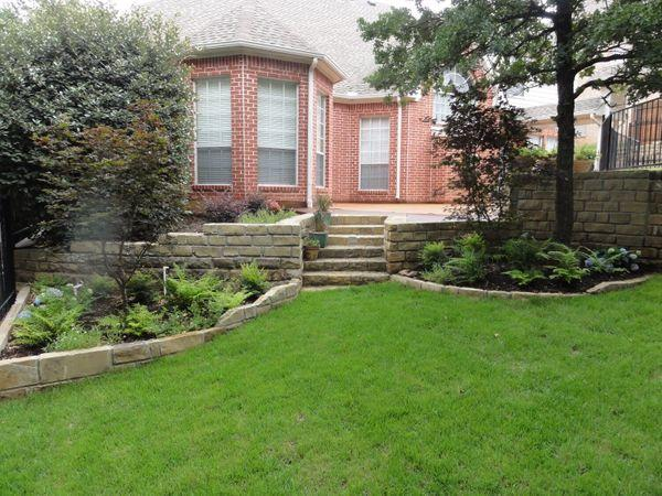 Backyard with traditional landscaping and new stone work
