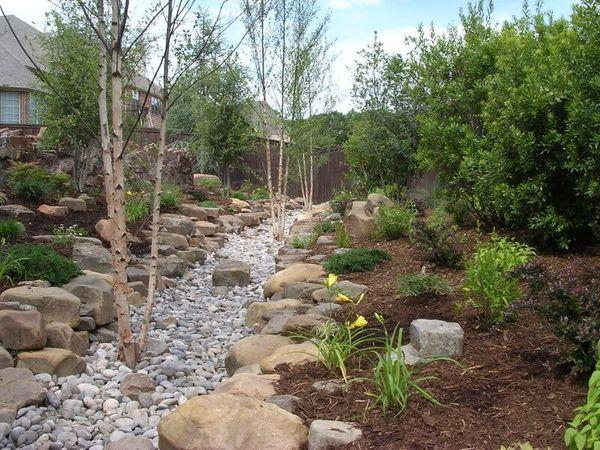 Residential landscape that includes native landscaping and stonework